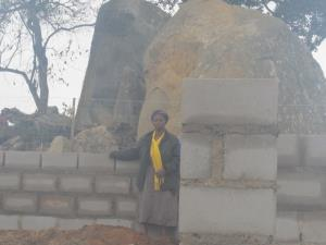 Nomsa is standing with the Care Center-in-progress